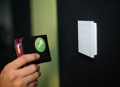 Dłoń trzymająca portfel z nalepką smart tag zbliża się do NFC Code Touch