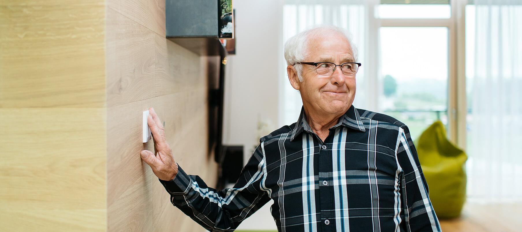 starszy pan w domu dotyka przycisku na ścianie