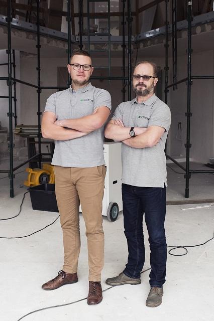 Dwóch uśmiechniętych mężczyzn stoi obok siebie z założonymi rękami