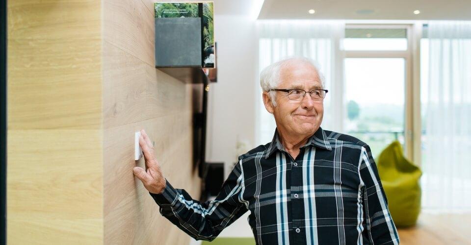 Starszy mężczyzna włącza przyciskiem światło