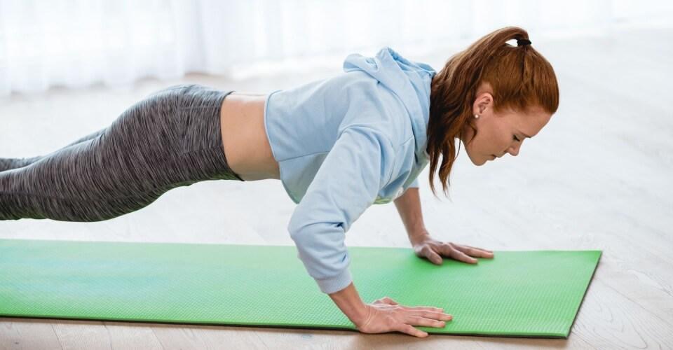 Ruda dziewczyna ćwiczy na macie jogę