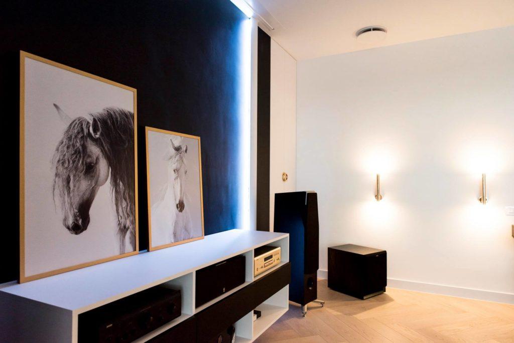 Oświetlony pokój z portretami koni