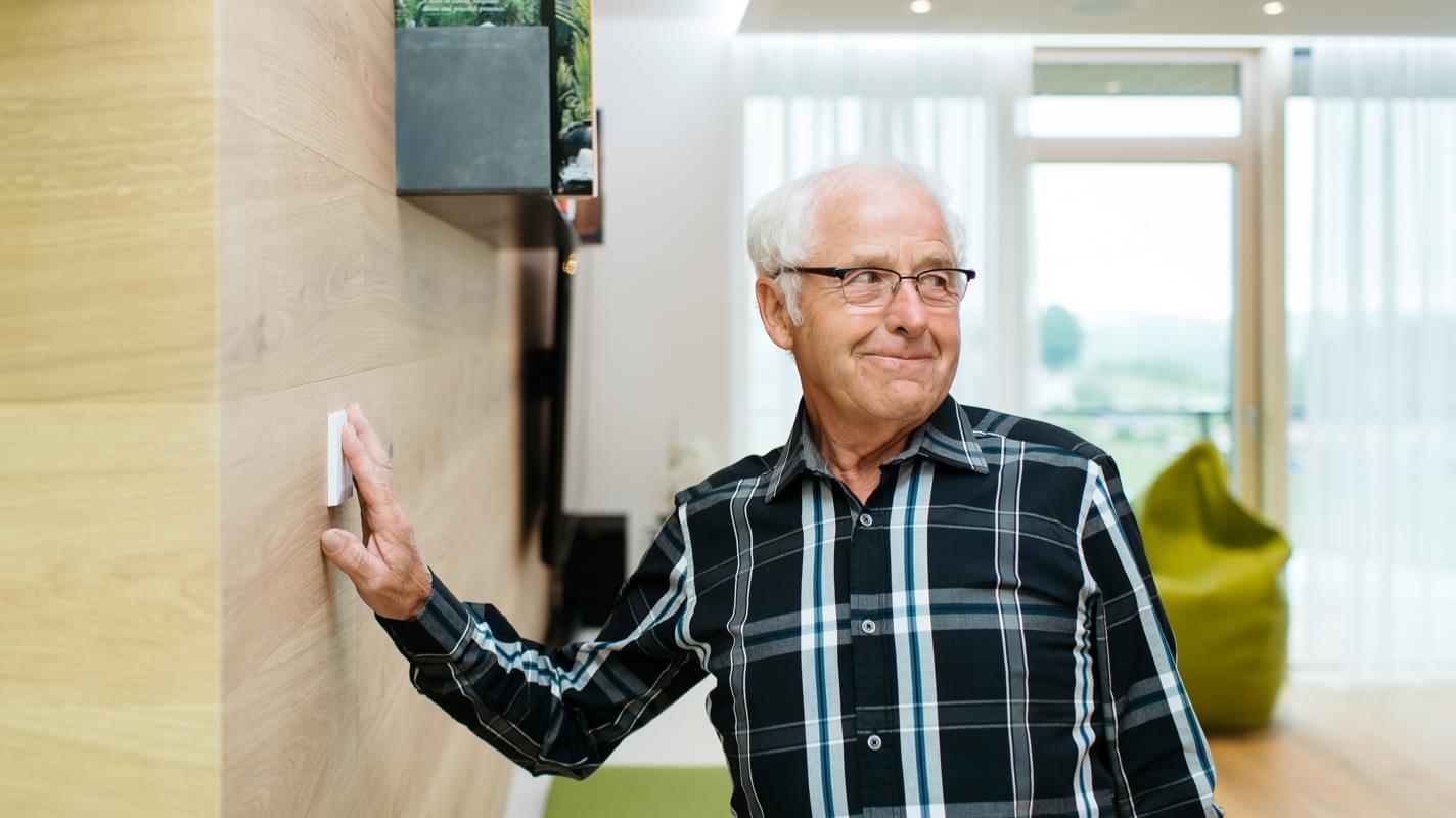 Senior używa inteligentnego włącznika Touch