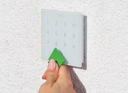 Kobieca ręka dotyka zielonym przyciskiem NFC białego panelu numerycznego