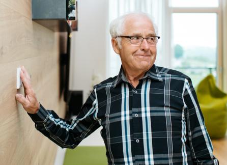 Starszy mężczyzna używa włącznika na ścianie