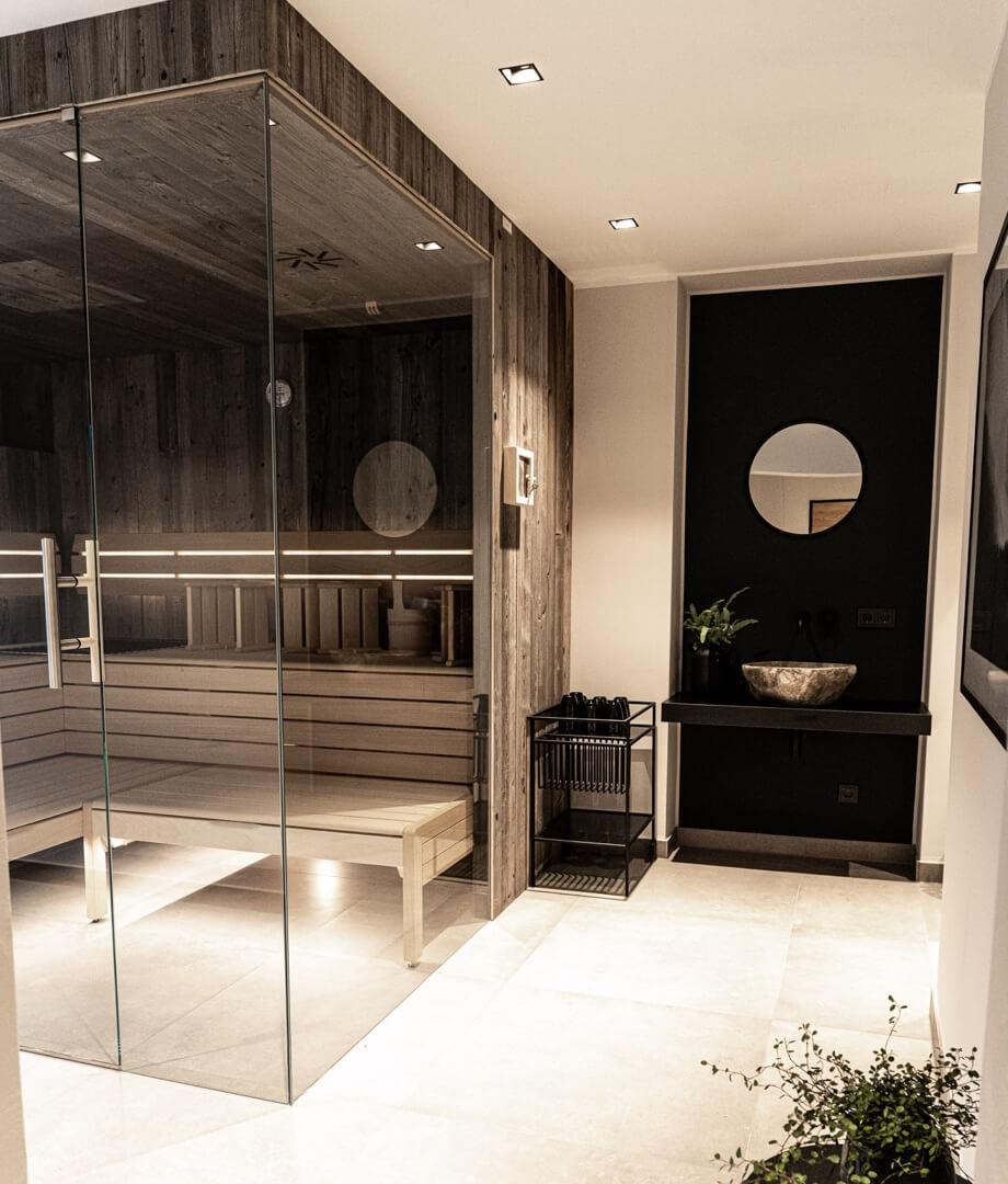 Jasny hol z białymi kafelkami i oświetlony białym światłem. Po lewej stronie jest oszklona sauna.