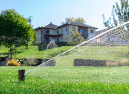 Zraszacz nawadnia trawnik. W tle jest dom.