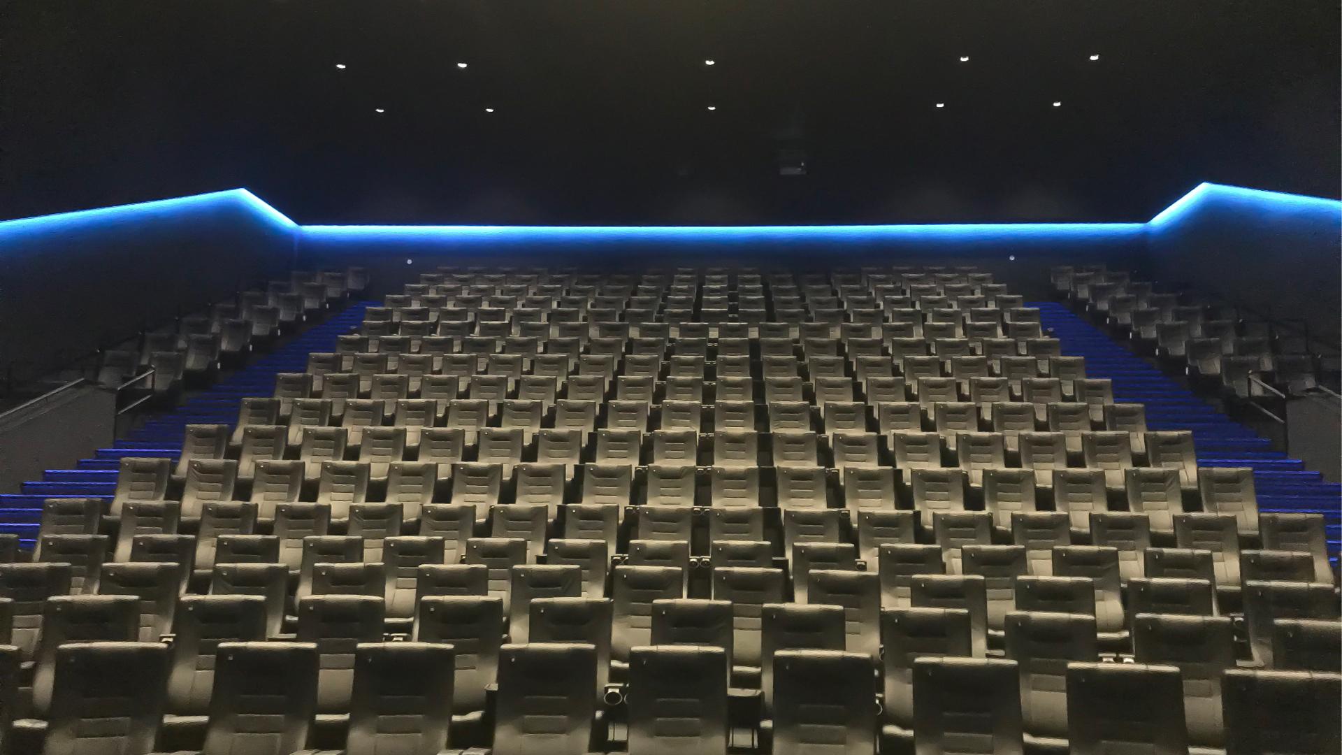 Sala kinowa z zielonymi fotelami i niebieskim światłem w tle