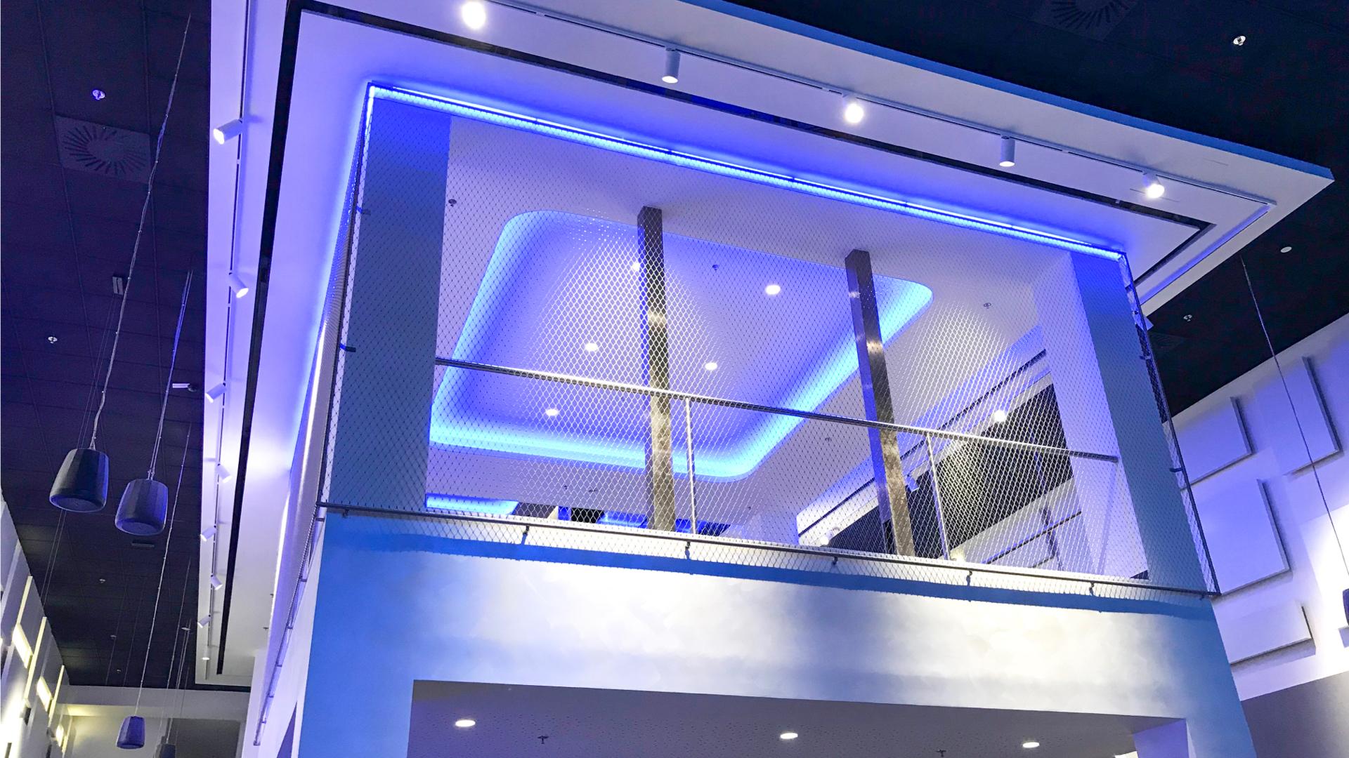 Biały taras w środku kina oświetlony niebieskimi światłami LED