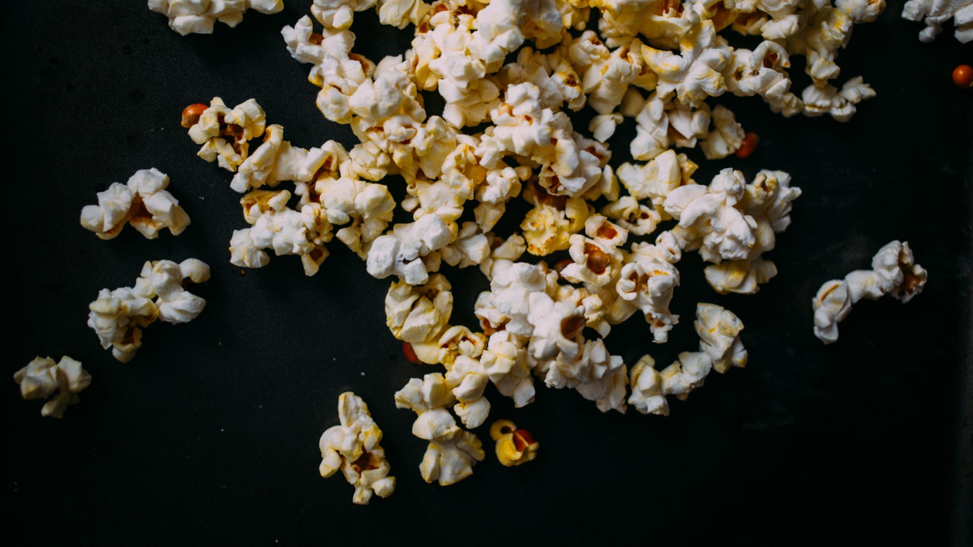 Rozsypany popcorn na czarnym tle
