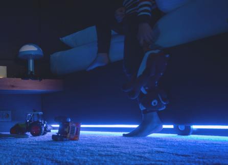 Dziecko schodzące z łóżka w nocy. Pod łóżkiem jest niebieskie światło
