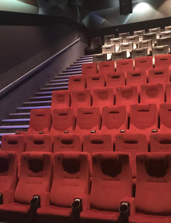 Fragment oświetlonej sali kinowej. Na dole czerwone fotele a na górze kremowe.
