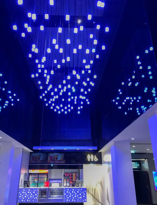 Górna część holu w kinie. Z sufitu zwisa niebieskie oświetlenie.