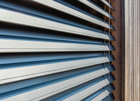 Szare rolety w brązowym oknie