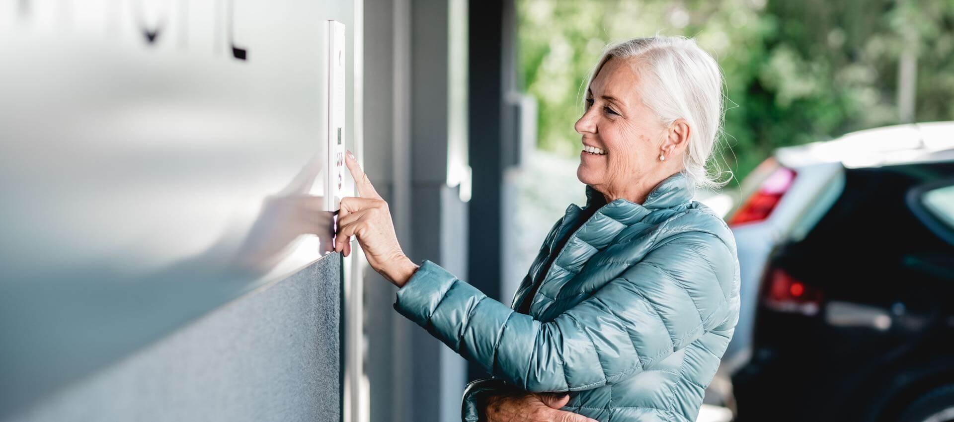 Staršia žena ovládajúca Intercom v exteriéri domu
