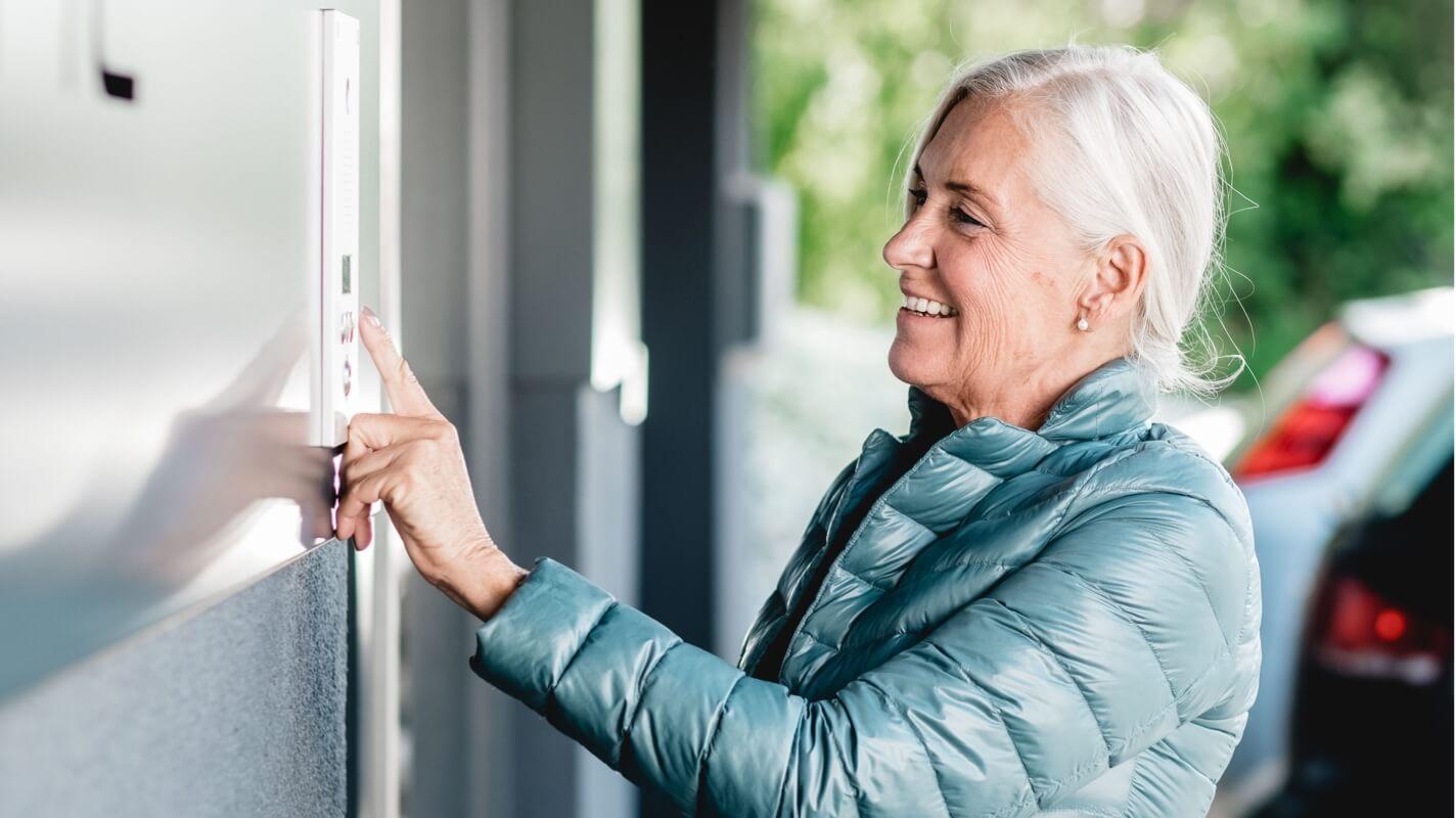 Staršia žena zvoniaca na vonkajší zvonček