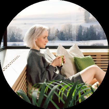 Žena oddychujúca na pohovke s čajom v ruke